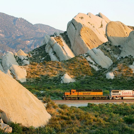A freight train moves through Cajon Pass and past the distinctive Mormon Rocks in California's San Bernardino National Forest.