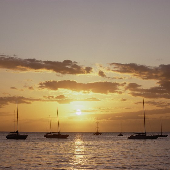 Sailboats perch off Maui's calm coastal waters at dusk.