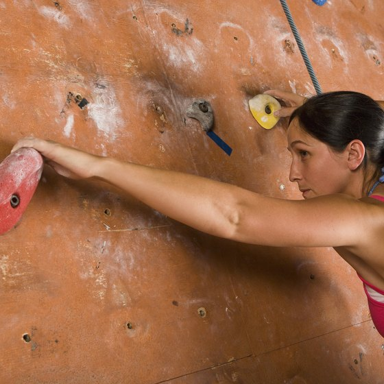 Beginners can learn how to rock climb by practicing on indoor rock climbing walls.