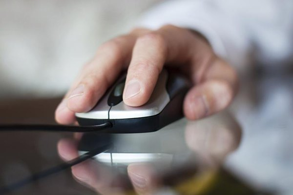 Hand clicking a computer mouse