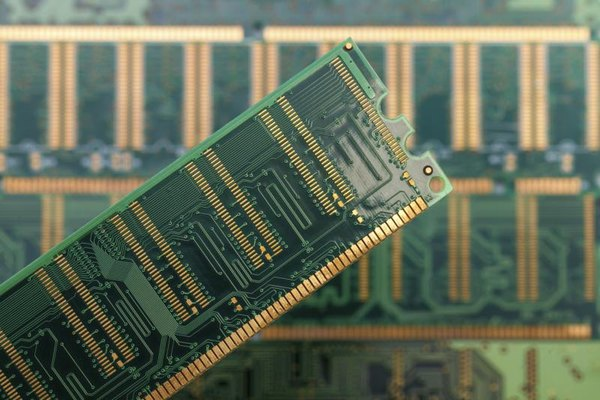 Close-up of a stick of computer RAM being held above several other sticks
