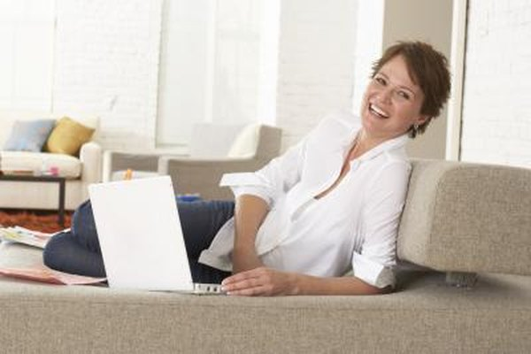 A woman is smiling on her couch with her laptop.