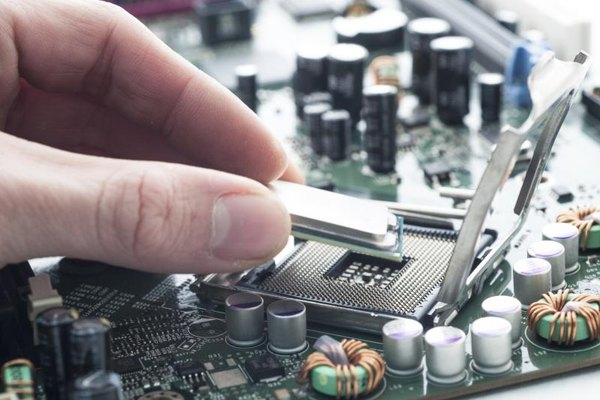 Close-up of a hand inserting a chip onto a computer motherboard