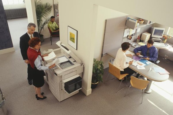 Office people using a copier and scanner.