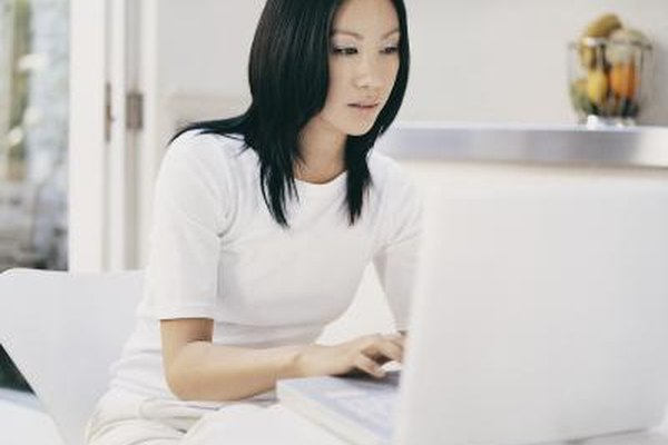 A young woman typing on a laptop computer