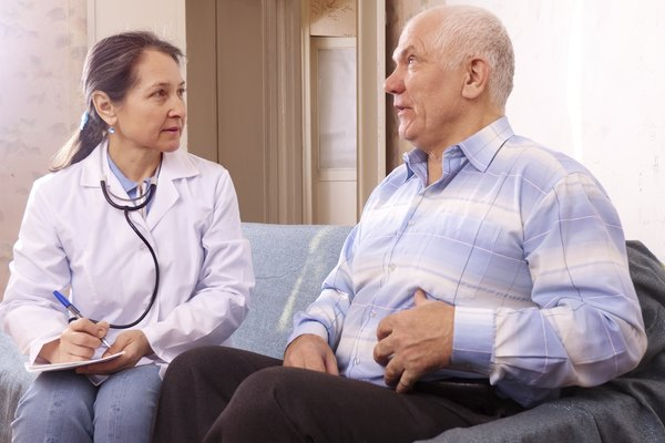 Mature man complaining  to doctor about tummy-ache