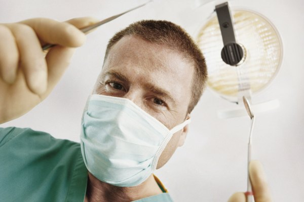 View Directly Below of a Male Dentist Wearing a Face Mask and Holding a Dental Scaler and Mouth Mirror