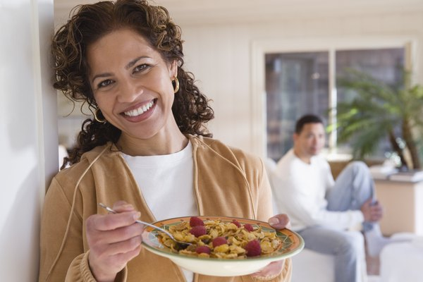 Smiling woman eating cereal with fruit