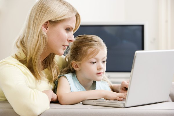 Girl and mother using laptop