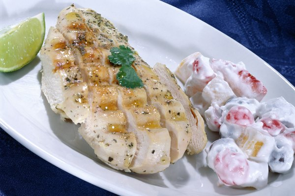A close-up of a boneless chicken breast and fruit salad
