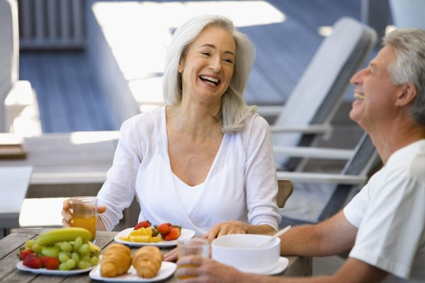 Couple laughing by plates of fruit