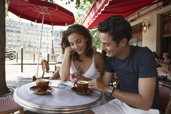 France, Paris, young couple writing postcards at cafe table