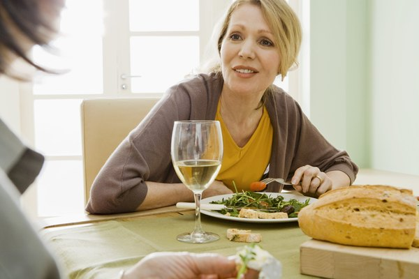 Women eating meal with wine