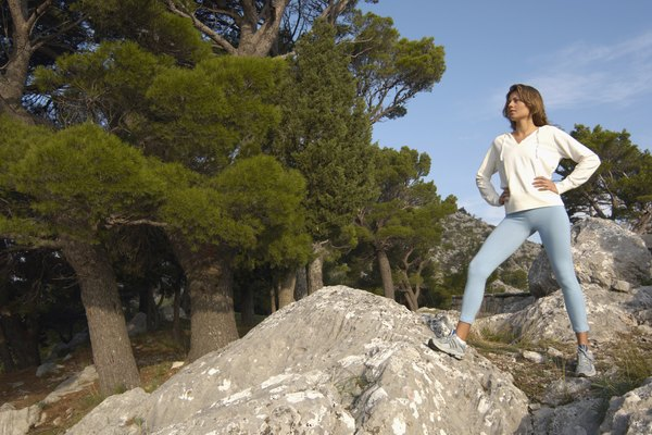 Young woman on rocks in mountain landscape, low angle view