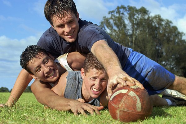 Three teen boys playing football and lying on the grass after a tackle