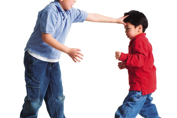 a little asian boy picks on his little brother as the two of them fight