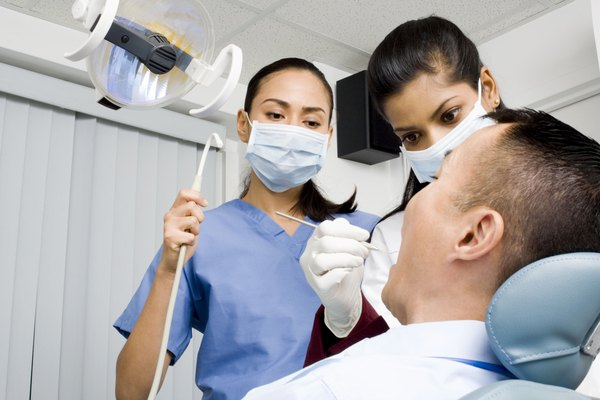 Dentist and dental hygienist performing procedure on patient