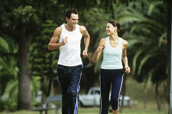 Mid adult man and woman jogging in park,looking in eyes and smiling