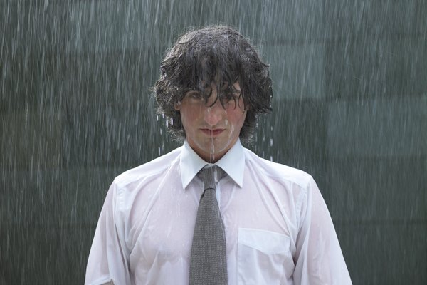 Young businessman standing in rain, portrait, close-up