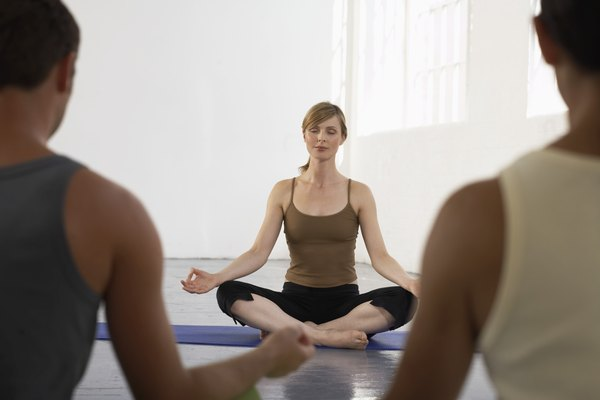 Yoga teacher sitting in sukhasana at front of class, eyes closed