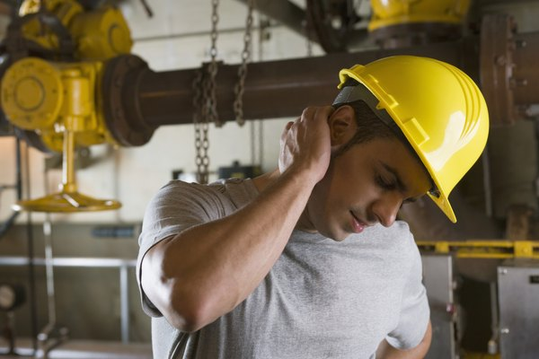 Worker wearing hardhat and experiencing neck pain