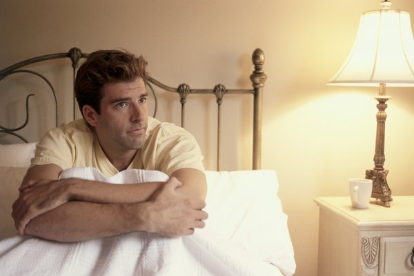 Young man sitting in bed