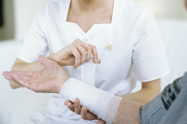 Nurse wrapping bandage around patient's wrist