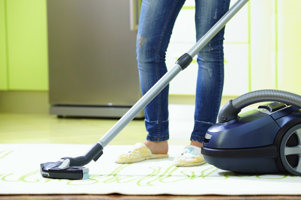 woman cleaning home with vacuum cleaner