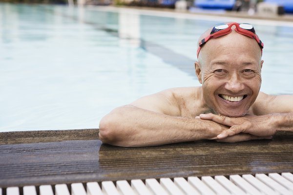 Smiling senior man swimmer wearing goggles