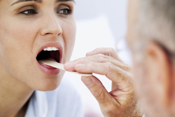 doctor examining with a woman with a tongue depressor