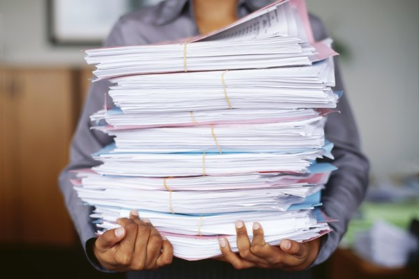mid section view of a man carrying stack of papers in an office