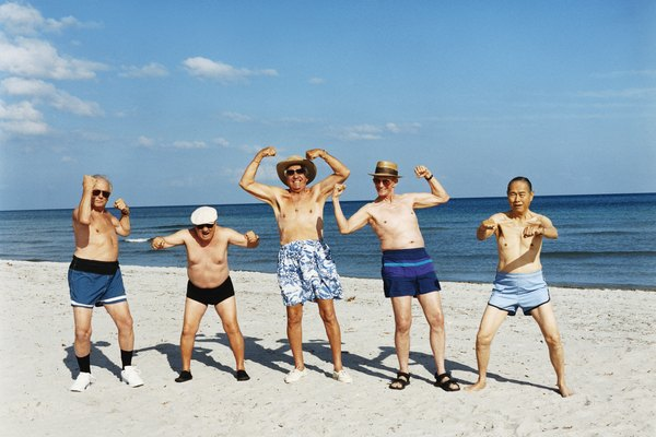 Five Senior Men in Swimming Trunks Stand on the Beach Flexing Their Muscles
