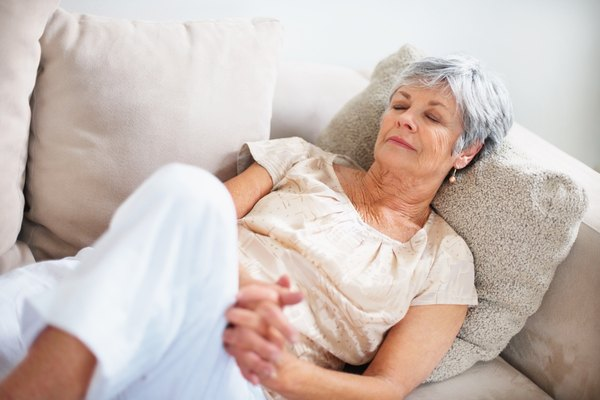 Elderly woman lying with eyes closed on couch