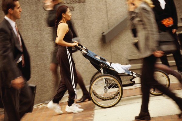 Woman in exercise clothes, pushing three-wheeled baby carriage