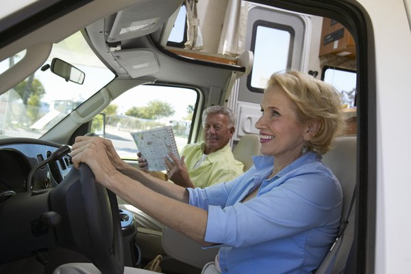 Senior Woman Sits in the Driver's Seat of a Motor Home, Her Husband Sitting by Her Looking at a Map