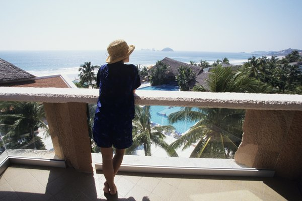 Woman on balcony overlooking ocean, Ixtapa, Mexico, Rear view