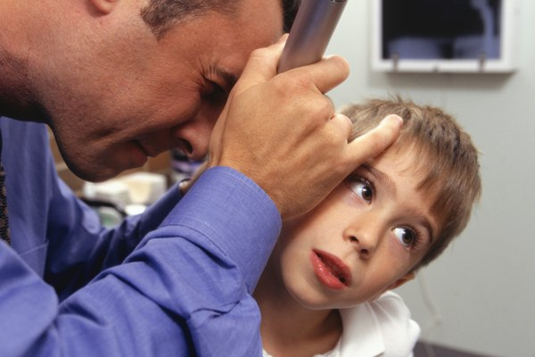 Boy (6-7) having ears checked up by doctor