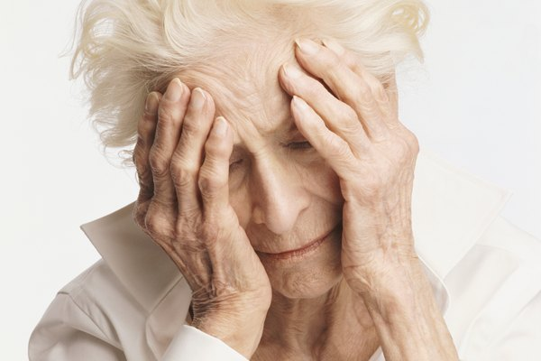 Senior Woman Looking Down With Her Head in Her hands