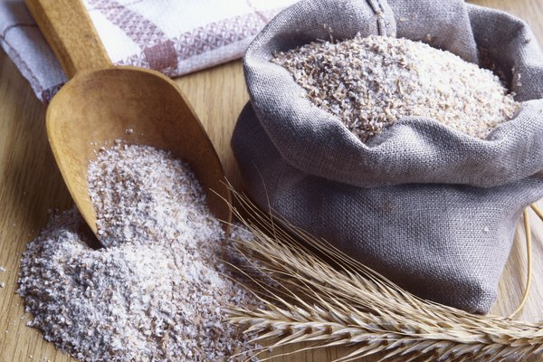 Still life of wheat flour with wooden scoop