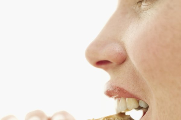 side profile of a young woman biting into a sesame seed cracker