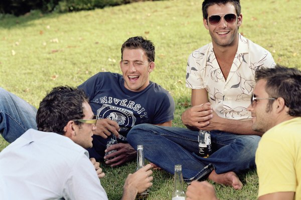 Group of young men relaxing outdoors, drinking beer, laughing