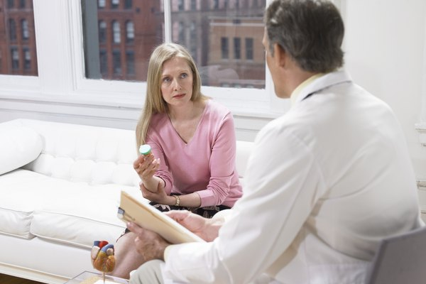 Woman Holding a Pill Bottle and Listening to Her Physician's Explanations