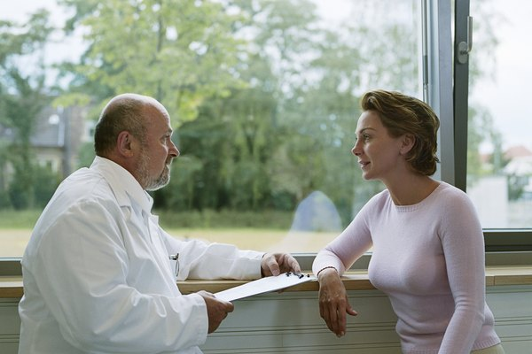 Male doctor sitting with female patient by window, side view