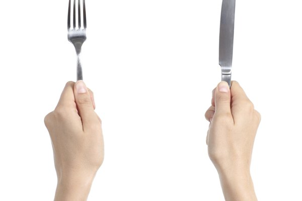 Woman hands holding a fork and knife