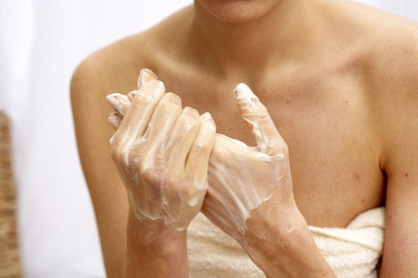 Young woman rubbing creme into hands, mid section, close-up