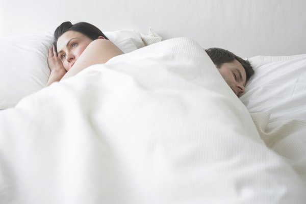 Couple lying back to back in bed, man asleep