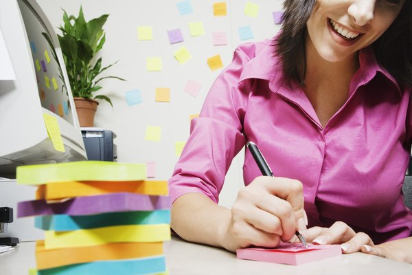 Woman writing next to stack of sticky notes