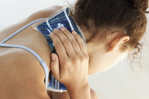 close-up of a young woman applying an ice pack to her neck