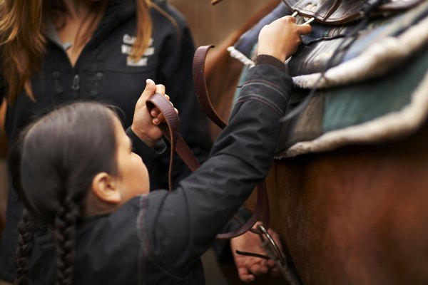 Woman helping girl saddle horse