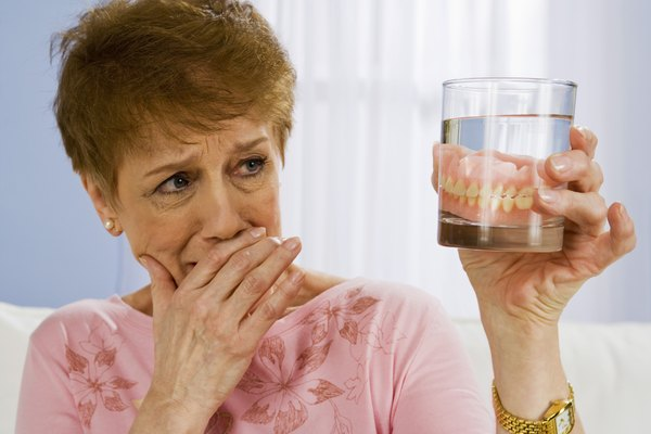 Woman with dentures in glass of water